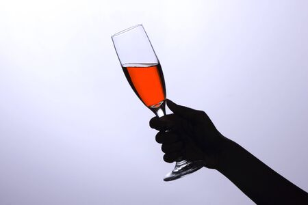 Hand holding a glass with red wine