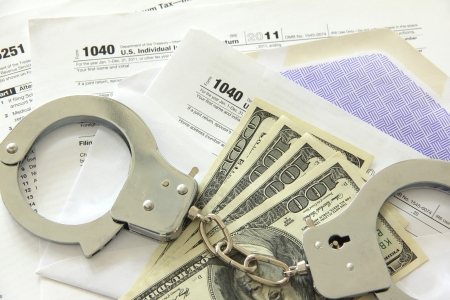 Tax papers in an envelope with dollar bills and handcuffs