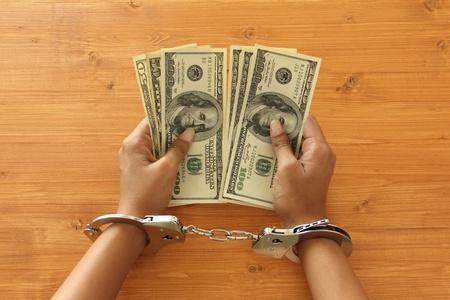 jailed: Prisoner with handcuffs holding dollar bills Stock Photo