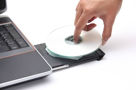 dvdr: Person placing a CD in a laptop cdrom drive
