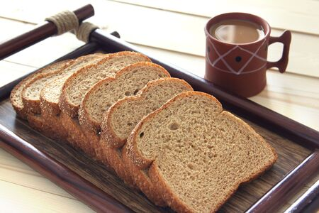 Tray of bread with coffee placed on a patio table Stock Photo