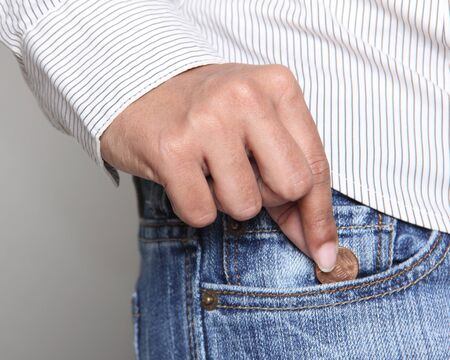 Bankruptcy - Person taking a penny from her jean pocket Stock Photo