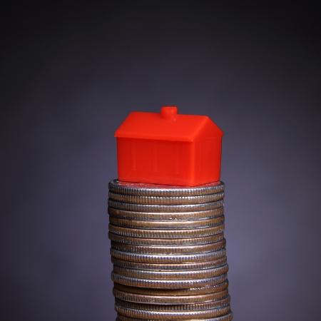 equidad: Hipoteca - icono de la casa en una pila de monedas Foto de archivo