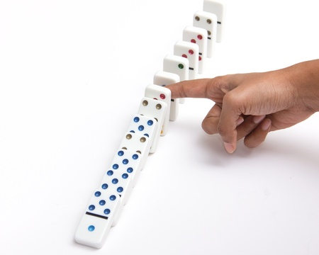 prevent: Person stopping the dominoes from falling