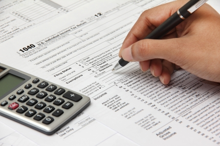 income tax: Person completing 1040 tax form with calculator