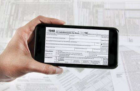 Filing taxes online using a mobile phone and internet Stock Photo
