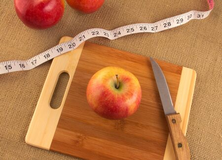 Healthy diet and nutrition for weight loss concept using apple and measuring tape