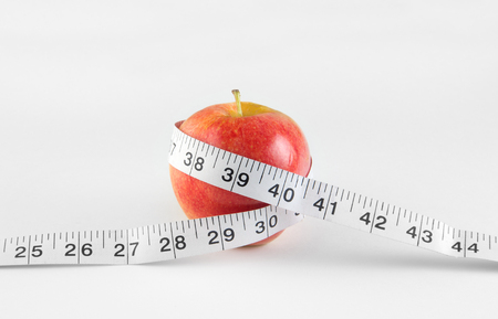 Nutrition and healthy diet concept with apple and measuring tape Stock Photo