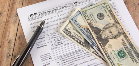 1040 tax form with calculator and dollar bills photo