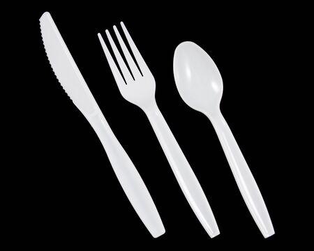 White plastic knife, fork and spoon on black background. Reklamní fotografie
