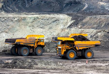 big mining trucks unload coal Standard-Bild