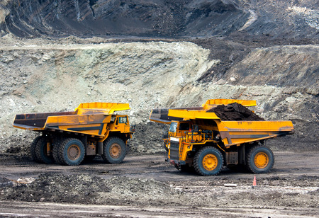 big mining trucks unload coal Stock Photo