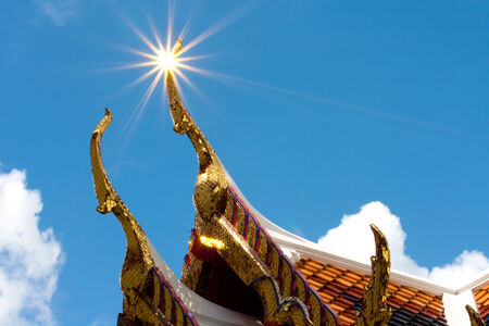light on temple roof, thailand photo