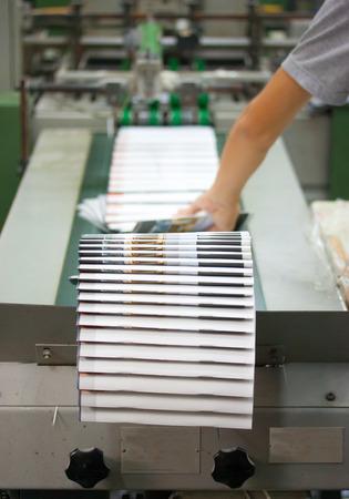 Print shop - Finishing line  Post press finishing line machine  cutting, trimming, paperback  Foto de archivo