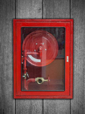 Red Fire Hose Cabinet on wood background