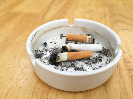 Burning cigarette on wood table photo