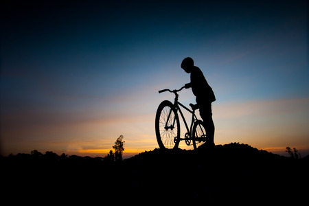 cycler: silhouette of children and bicycle at sunset
