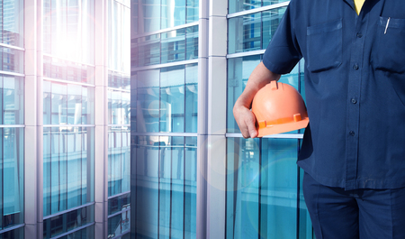 color tone: engineer holding orange helmet for workers security on office buildings in blue color tone