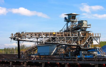 stockpile: Large conveyor belt carrying coal and emptying onto a huge pile.