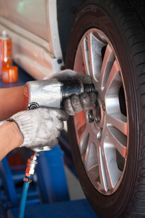 unscrewing: car mechanic screwing or unscrewing car wheel of lifted automobile by pneumatic wrench at repair service station - fofus hand tool
