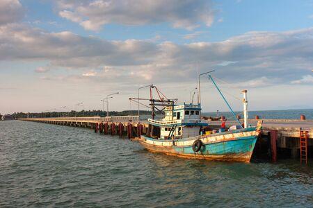 fishing pier: Fishing boats moored alongside the pier