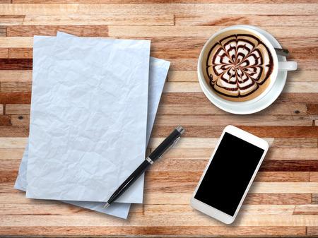 紙、スマート フォン、ペン、木製のオフィスの机の上のコーヒー カップに平面図です。