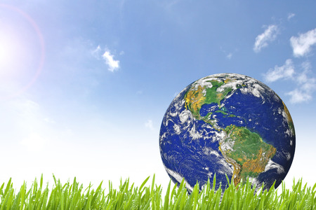 the natural world: Planet Earth on beautiful green grass and sunny day with blue cloudy sky