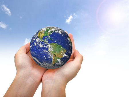 medioambiente: Earth planet in female hand and blue sky - Elements of this image furnished by NASA Foto de archivo