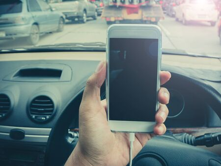 travelling salesman: man using a smartphone while driving a car with a filter effect
