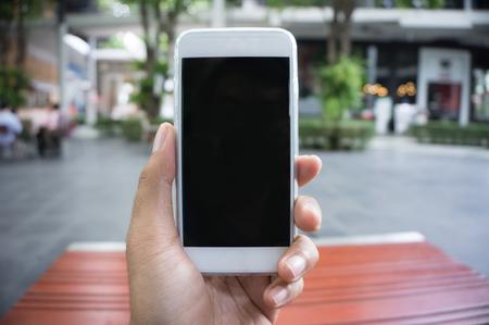 bonhomme blanc: La main de l'homme montre mobile smartphone en position verticale, arrière-plan flou - modèle maquette Banque d'images