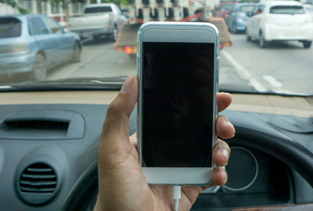 travelling salesman: man using a smartphone while driving a car
