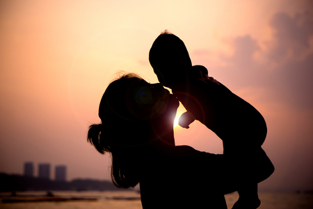 madre y bebe: Silueta de la madre con su niño en contra de la puesta de sol y lentes flare