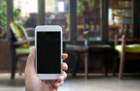 verticales: La mano del hombre muestra el smartphone móvil en posición vertical, fondo borroso - plantilla de maqueta Foto de archivo