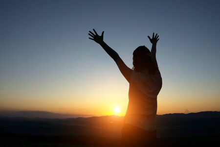 woman hands up: silhouette woman Hands up against sunset time with lens flare Stock Photo