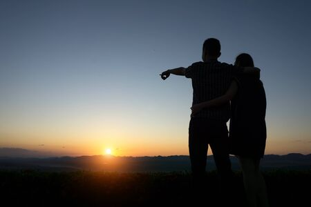 flare up: silhouette lovers Hands up against sunset time with lens flare
