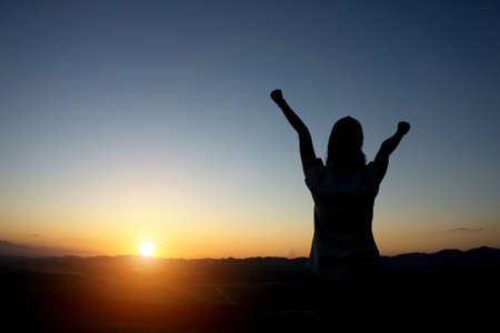 flare up: silhouette woman Hands up against sunset time with lens flare Stock Photo