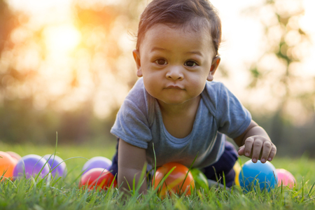 effect sunset: Cute asian baby crawling in the green grass and colorful ball - Sunset filter effect Stock Photo
