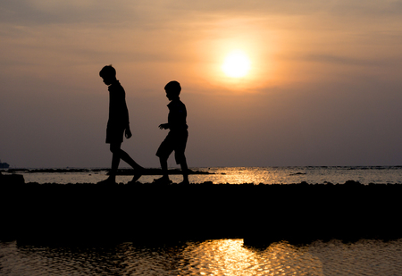 brethren: Silhouette group of child walking at sunset on the beach