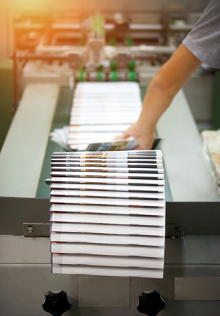 finishing line: Print shop - Finishing line. Post press finishing line machine: cutting, trimming, paperback. Stock Photo