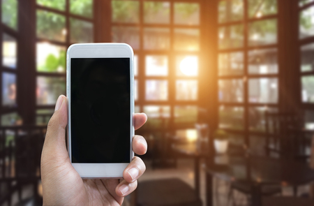 Mans hand shows mobile smartphone in vertical position and blurred background, You can use this smartphone with blank screen for your smartphone application presentation - smartphone mockup template Zdjęcie Seryjne