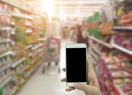 Female hand hold smartphone at supermarket and checking shopping list Stock Photo