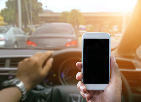 travelling salesman: Man using a smartphone while driving a car - Sunset filter effect Stock Photo