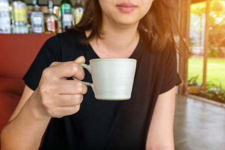 Close-up of female hand holding a cup of coffee Stock Photo