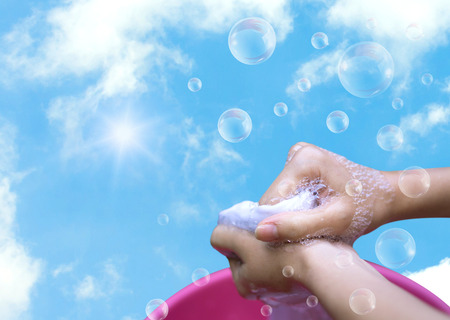 Female Hand washing clothes in the pink basin with clear Bubble soap against blue sky and sunlight. Stock Photo