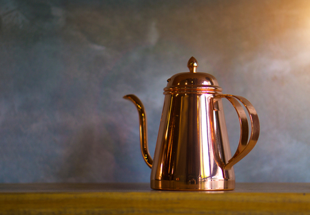 Copper coffee pots on wood shelf for home interior. Stock Photo