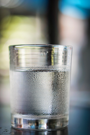 refle: Selective focus of Glasses water on a table.