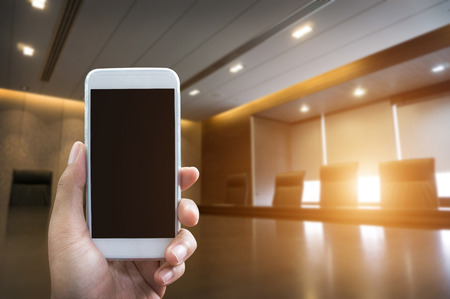 Mans hand shows mobile smartphone in vertical position and blurred meetingroom background - business mockup template