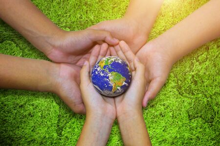 Earth planet in asian Children hand on green grass background. - Elements of this image furnished by NASA Stock Photo