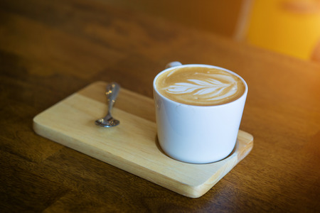 Hot latte coffee on wooden table. A latte is a coffee drink made with espresso and steamed milk. The term as used in English is a shortened form of the Italian. Stock Photo