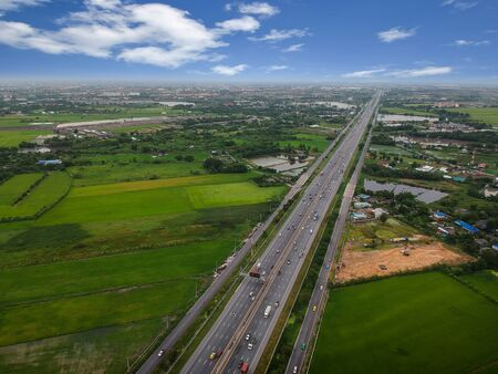 Aerial view of rural tree covered countryside with highway of road passing through farmland fields in Thailand, Viewed from above, Aerial view. Top view photo from Drone. Stock fotó